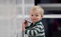 preschool boy drawing on whiteboard