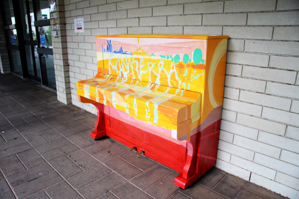 Multi-coloured piano against wall with Canberra written on it