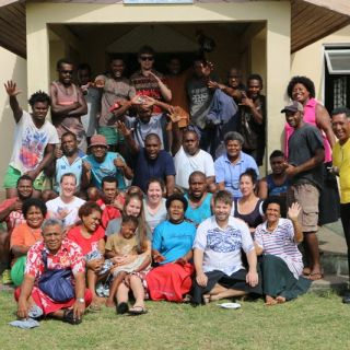 University of Canberra students and Fijian community members pose outside a building at the end of their study trip