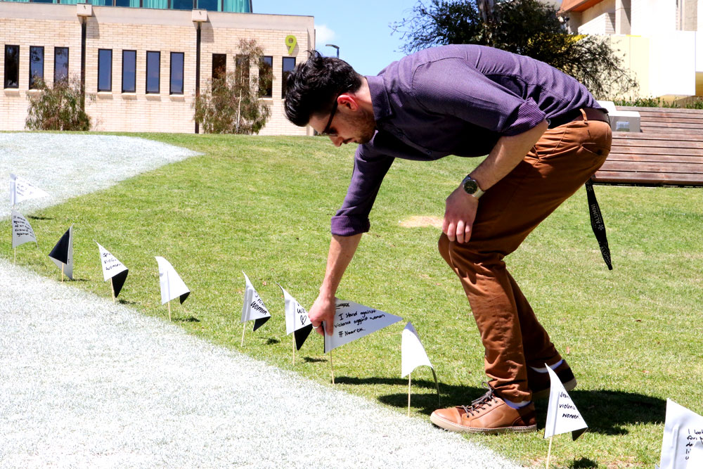 A staff member places a flag in the ground to support White Ribbon Day