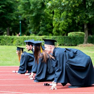 Students lining up for a race in graduation gowns