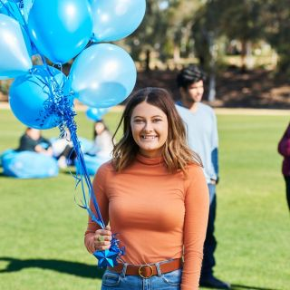 student with balloons