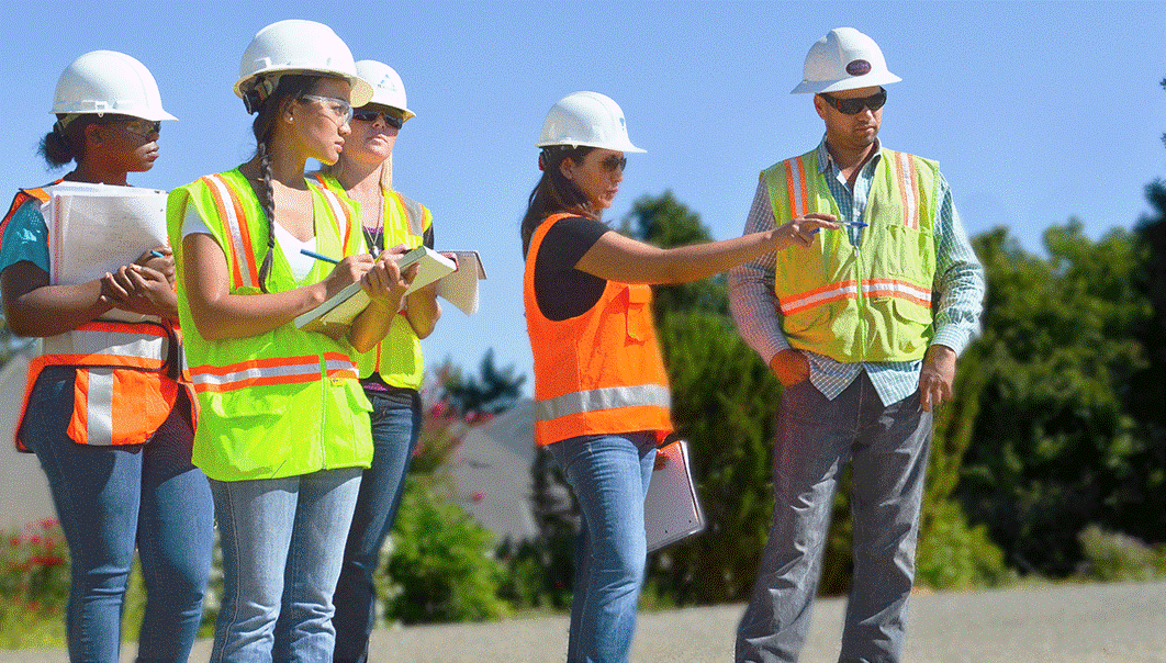 Four female construction workers in hi-vis vests and hard hats working with male construction worker