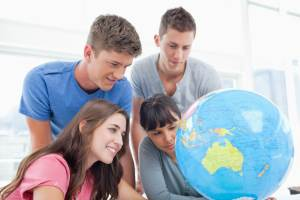 Four students studying a globe