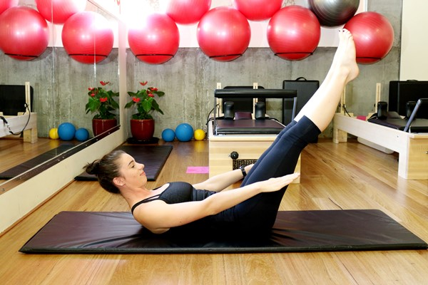Nia Southwell holds a Pilates pose, with her legs extended up at a 45 degree angle on a cushioned mat.