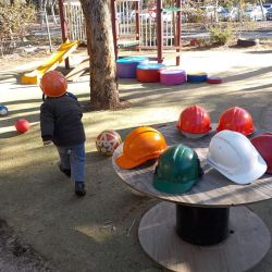 hard hats on a table, two children wearing hard hats, role playing