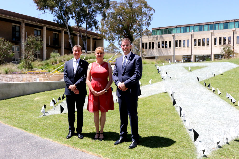 Professor Nick Klomp, Executive Director of the Domestic Violence Crisis Service Mirjana Wilson and Scott Pearsall stand in front of a giant white ribbon painted on the grass on the concourse.