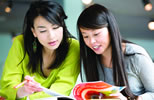 Two students reading an IELTS text book
