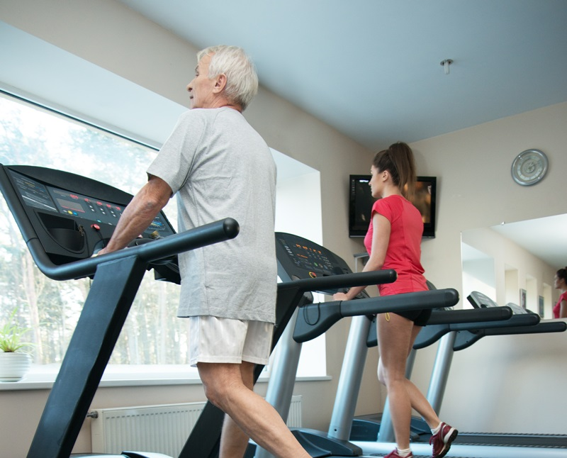 An older person using a treadmill at a gym