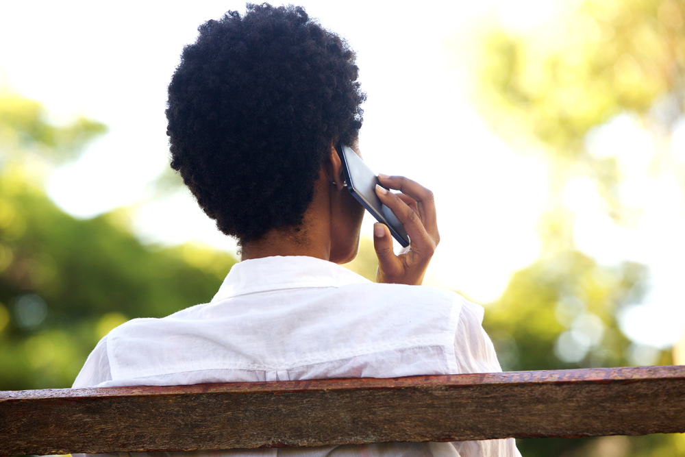 Image of a woman sitting on a park bench on the phone