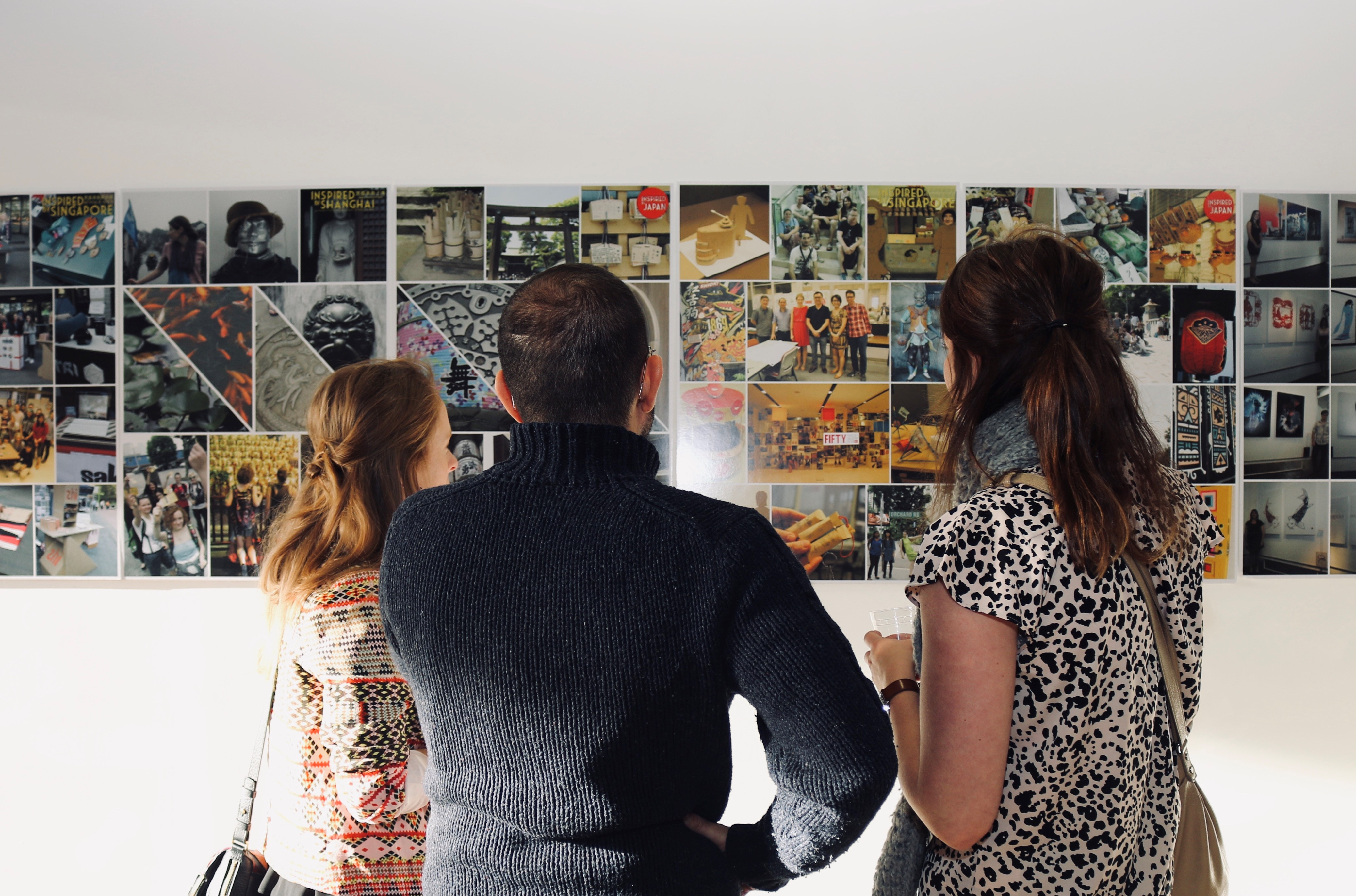 Three People looking at Wall Art of Students End of Year Exhibition Projects