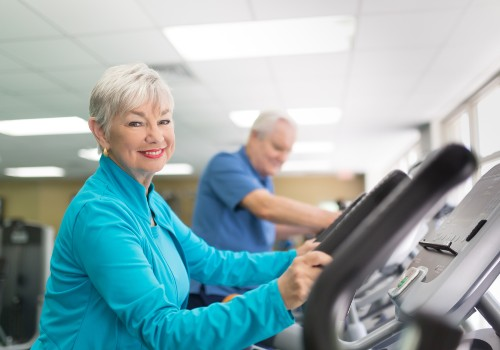 A senior woman using a treadmill and smiling at the Physiotherapy Parkinsons CLinic in the UC Health Hub.
