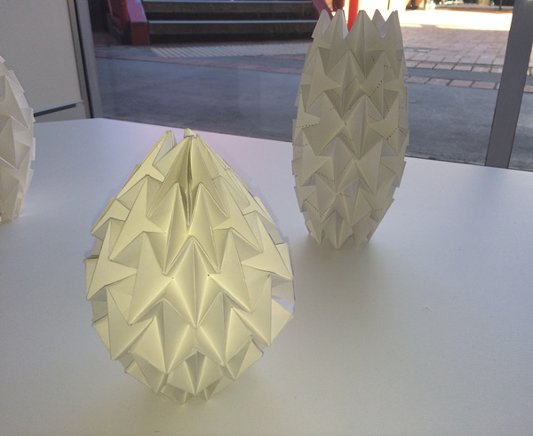 Lampshades made of folded white paper, featuring intricately folded shapes.