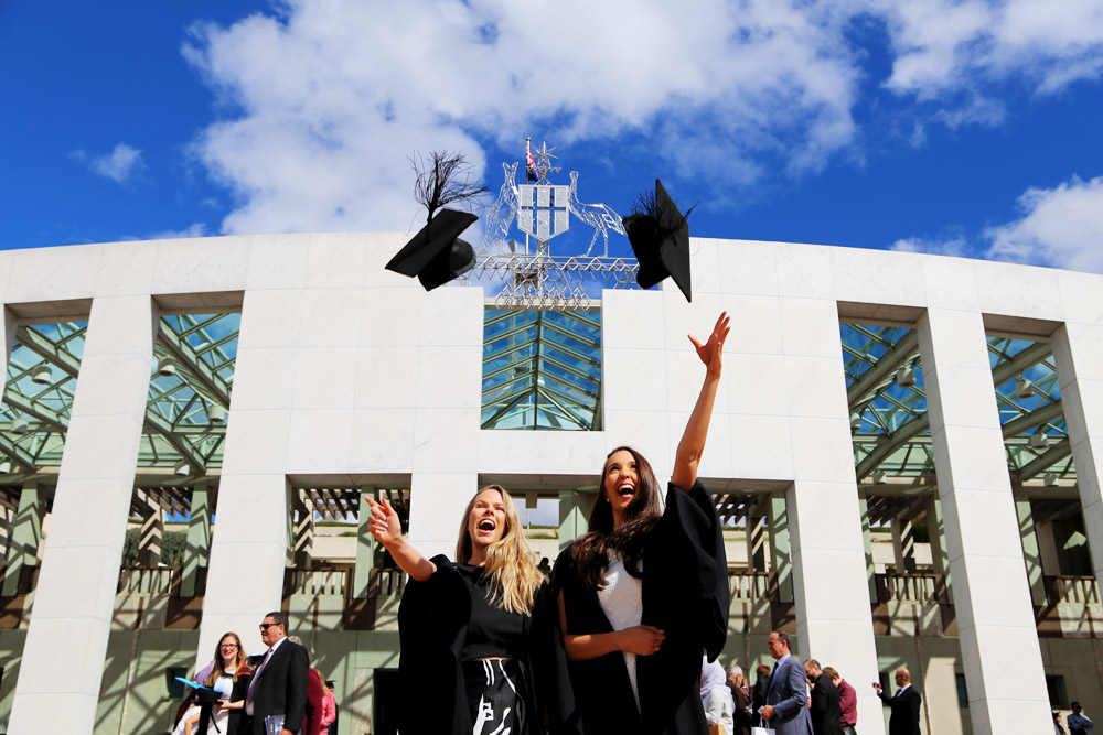 Two graduates throw their mortarboards in the air as they celebrate graduating from the University of Canberra