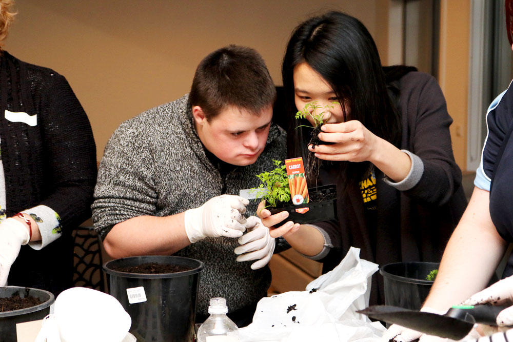 Nutrition and dietetics student Cathy Wong teaching resident Jordan how to plant a carrot seedling