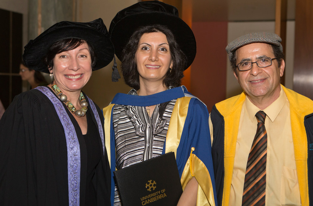 Graduate is in the centre holding her testamur with her supervisor and husband either side
