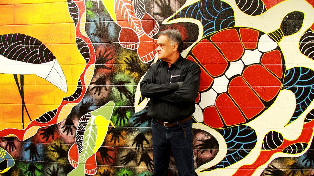 Paul Collis standing in front of Aboriginal artwork