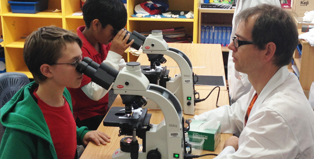 Image of a researcher teaching a student how to look through a microscope