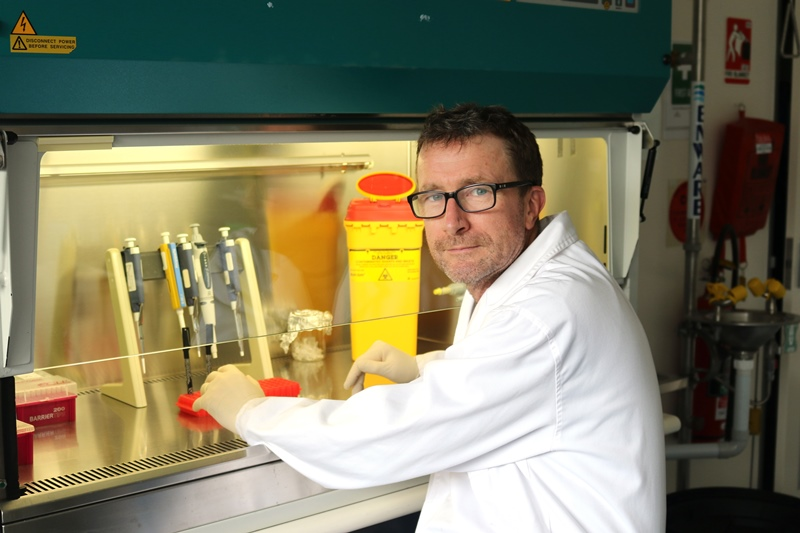 Dr Dennis McNevin sits at a fume-cupboard in his genetic ancestry lab