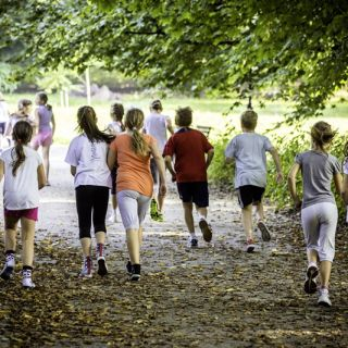 A group of primary school students running along a footpath
