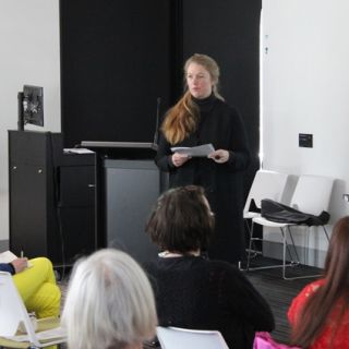 Poet and researcher Monica Carroll addresses the crowd of more than 50 at the Poetry on the Move Symposium