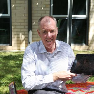 Centenary Professor Tom Lowrie sits outside with a Samsung tablet