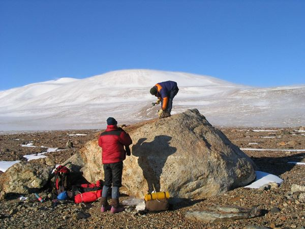 Dr Duanne White takes samples from a large boulder in Antarctica