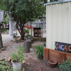 Outdoor area set up with furniture made from tree offcuts, curtains hanging in the trees and