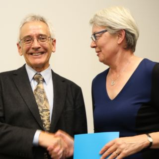 Centenary Professor John Dryzek accepts his award from DVC R&I Frances Shannon