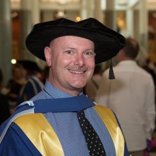 Dr Rob Stanton at his graduation ceremony decked out in his gown and bonnet