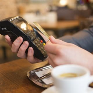 A person pays using contactless technology at a coffee shop