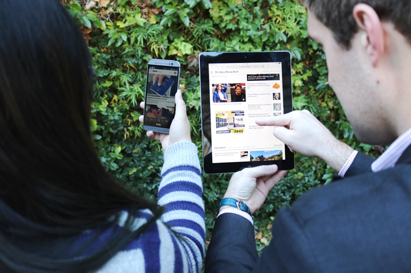 Two people viewing Digital News sites on a phone and tablet device
