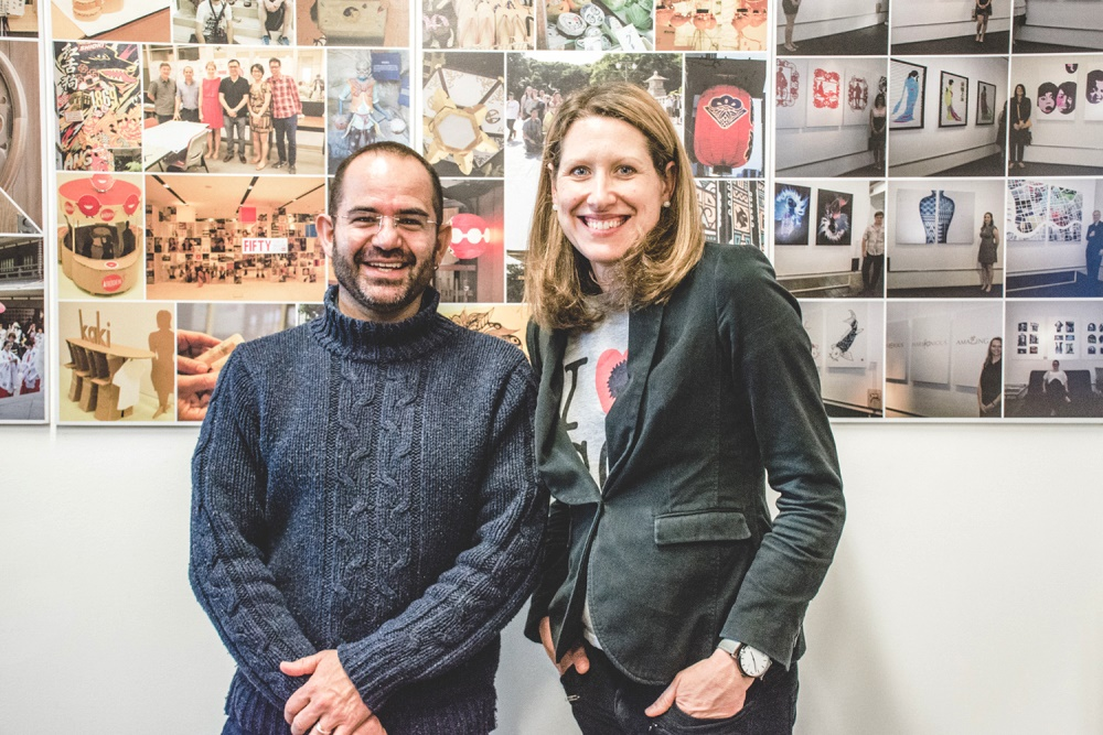 Carlos Montana Hoyos and Lisa Scharoun in front of a collection of photos of students design work