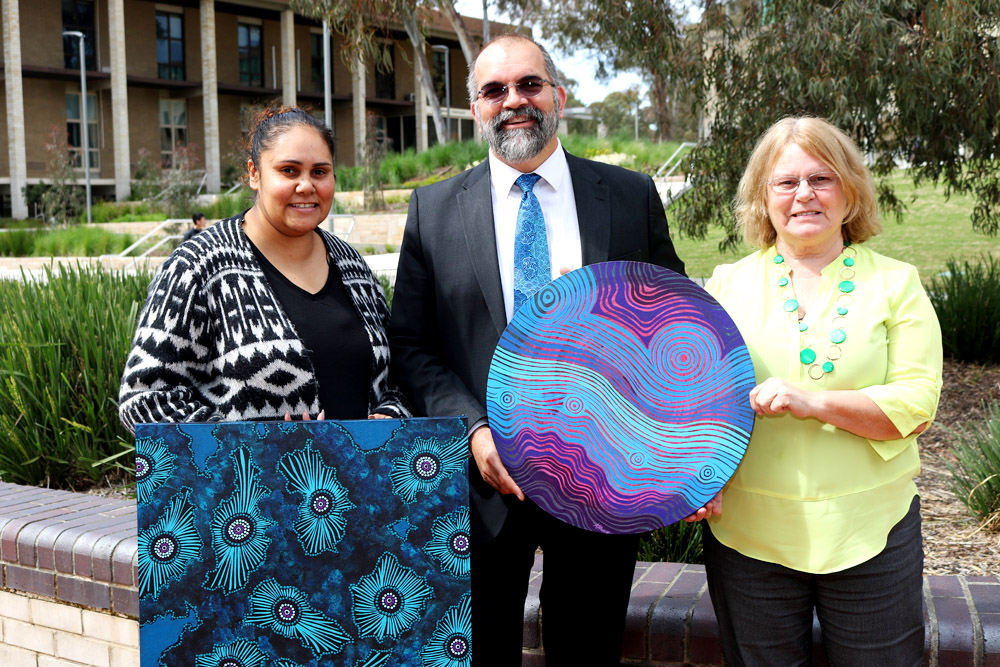 Tamara Murray, Professor Peter Radoll and Aunty Roslyn Brown with Krystal Hurst's artworks 'Waterholes and Ocean Waves' and 'Rock Pools'