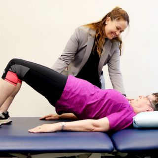 Kellie Toohey helps a woman stretch during the Cancer Rehabilitation exercise program for cancer