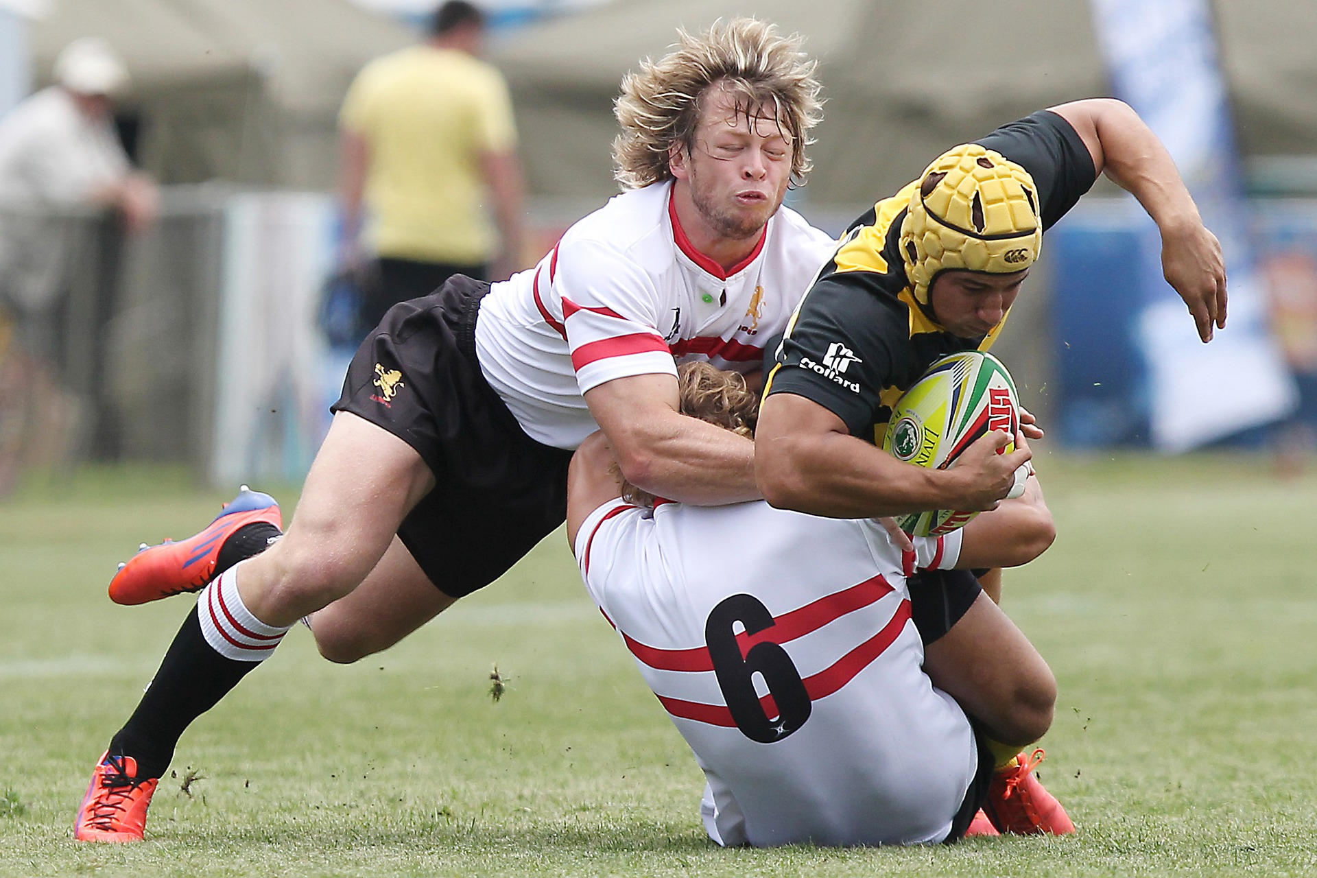 Two rugby players in white tackle an opposing player on the field who wears a protective yellow helmet.